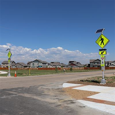 road with crosswalk signs on either side, neighborhood in background