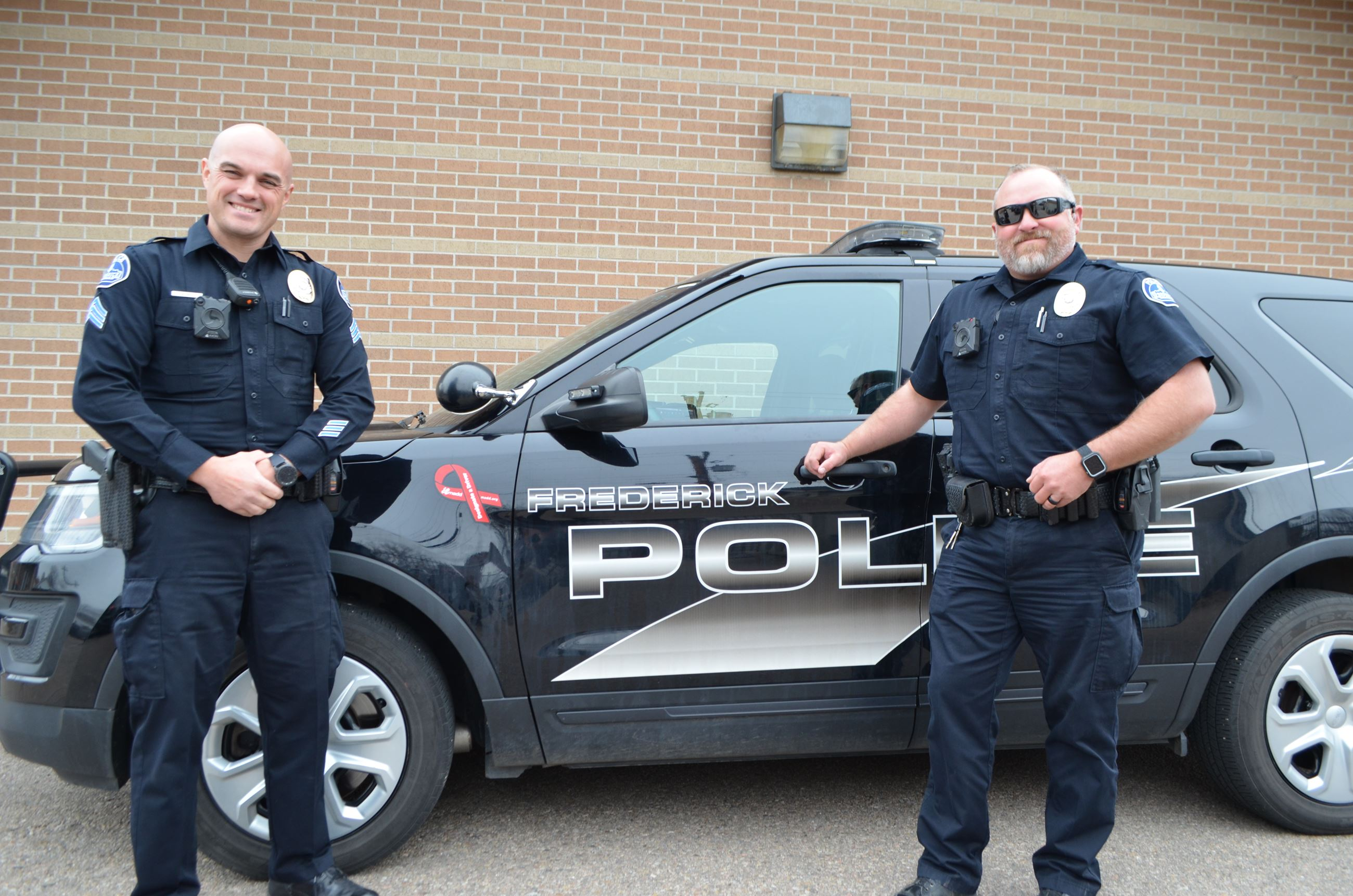 picture of two Frederick police officers standing by police vehicle