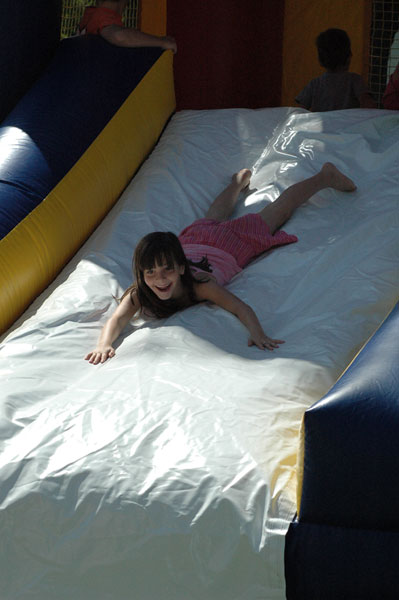 Girl sliding down inflatable slide at Miners Day